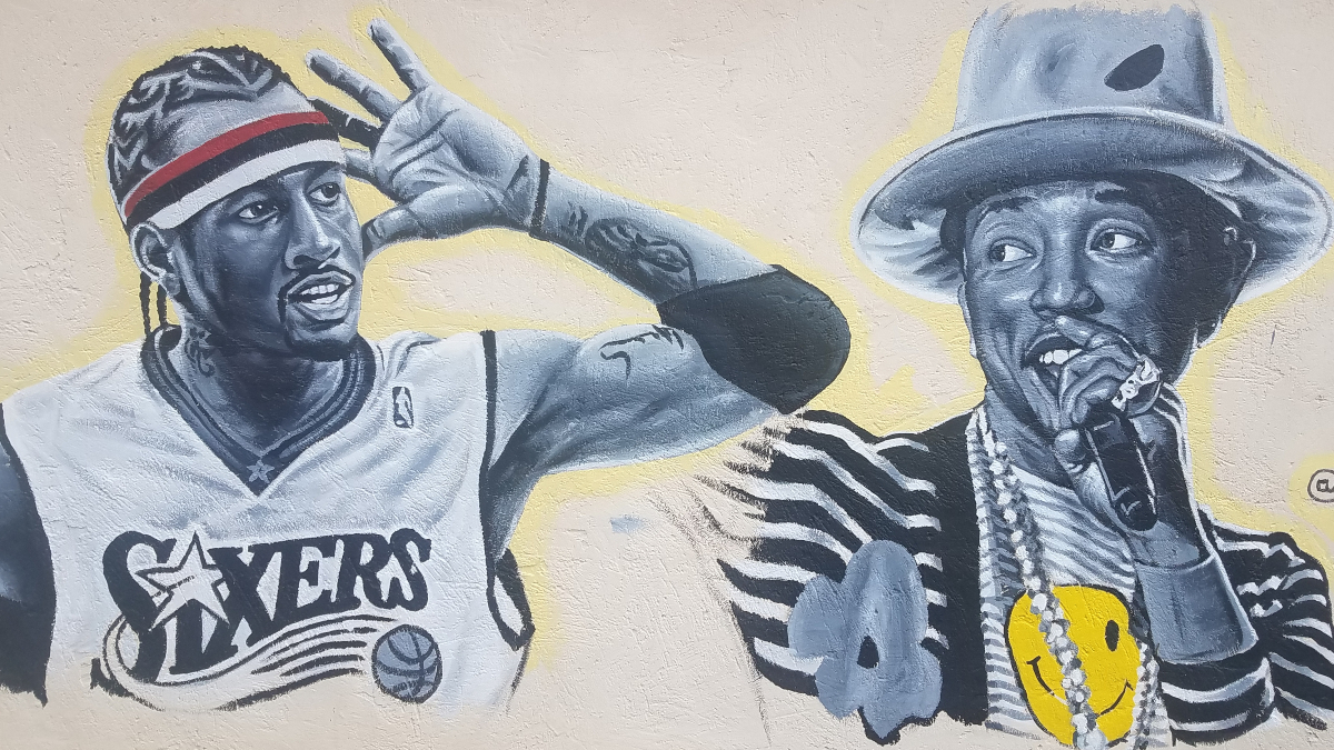 "Photo by Gina Gambony. Allen Iverson and Pharrell Williams on the side of ""Colleywood Cuts"" on Colley Avenue. Art by Brodrick Antoine."