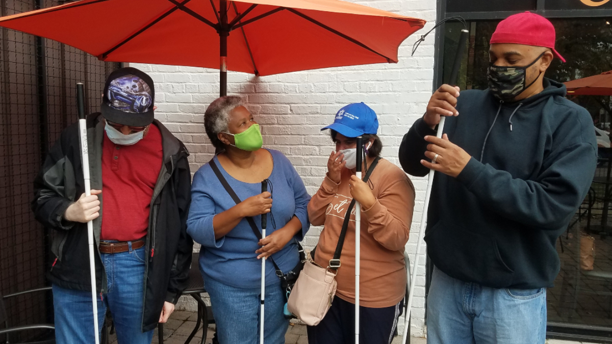 "Photo by Gina Gambony/WHRO. A group from the Tidewater chapter of the National Federation of the Blind gathers under an umbrella at Colley Cafe. October is ""Meet the Blind"" month."